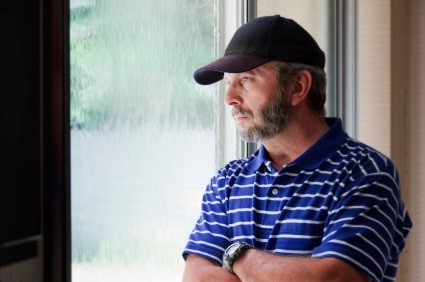 Depressed male looking out window